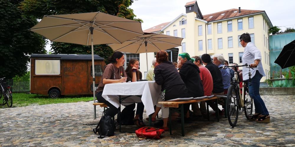 Tisch mit Gästen vor dem Diesel-Café mit Blick auf die Spinnerei