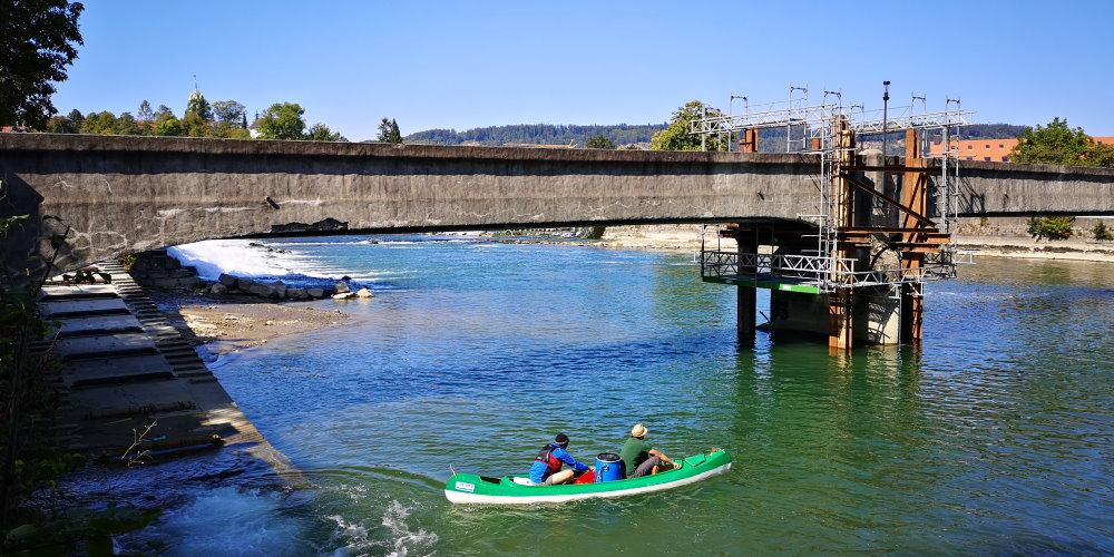 Kanu mit 2 Personen schwimmt vor der Reussbrücke, deren Pfeiler saniert wird