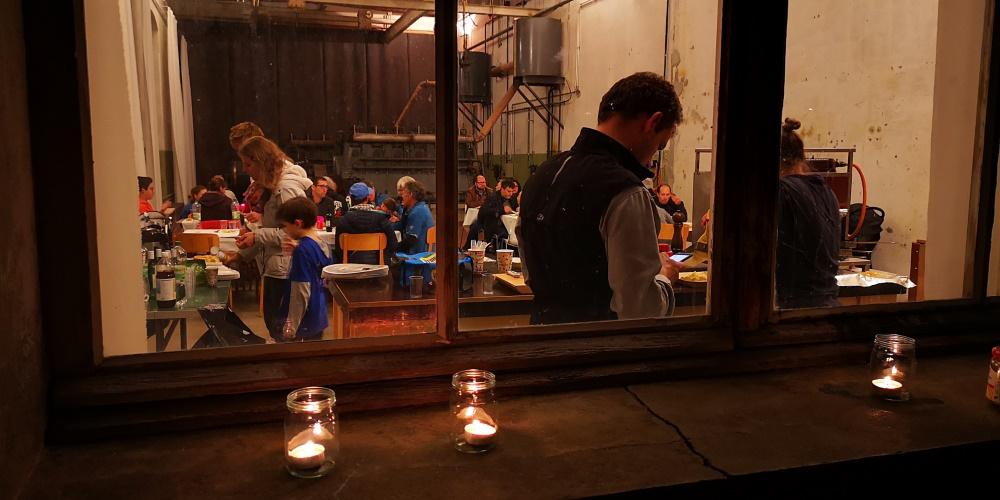 Blick von aussen durchs Fenster auf dessen Sims Kerzen stehen