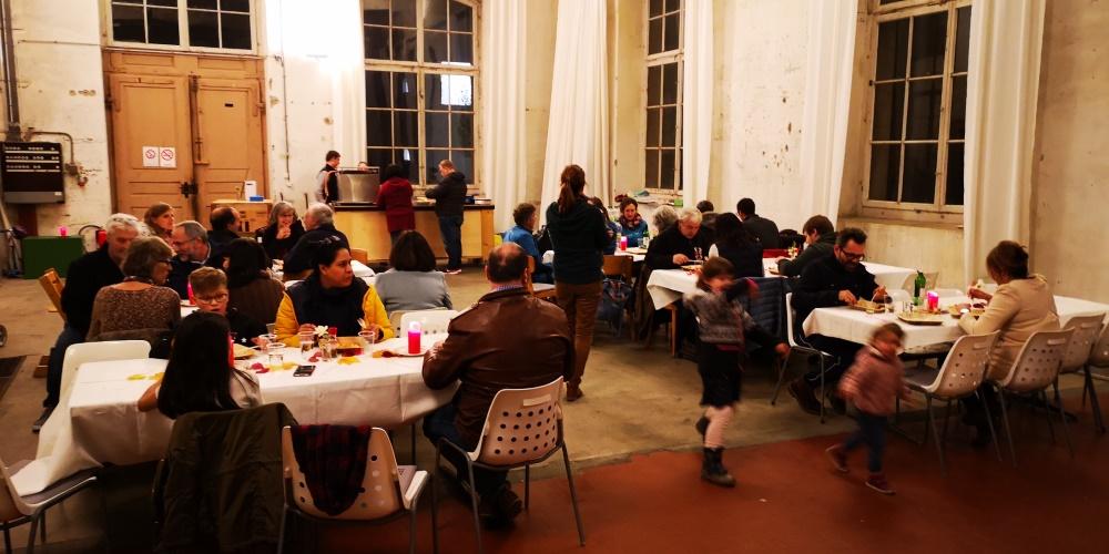 Voll besetzte Tische im Diesellokal mit Gästen beim Raclette-Essen